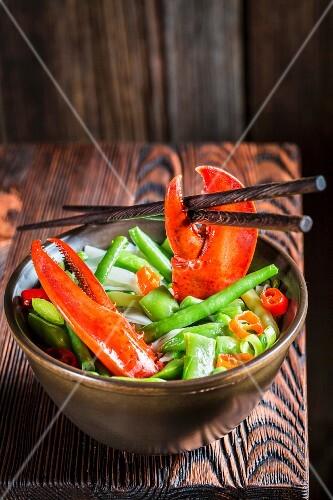 Nudeln mit Gemüse, Hummer und Essstäbchen (Asien)