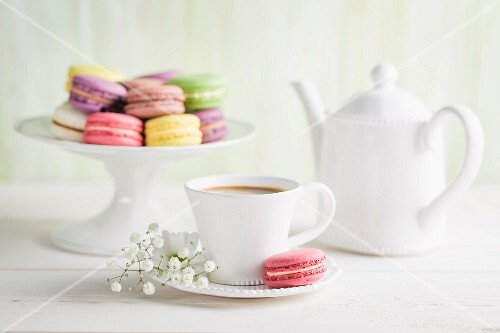 Colourful macaroons with coffee on a white table