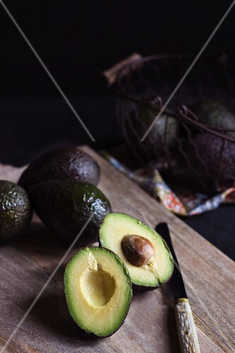 Whole avocados and a halved avocado on a wooden board