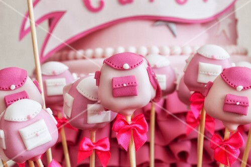 Pink cake pops shaped like schoolbags with a pink cake in the background