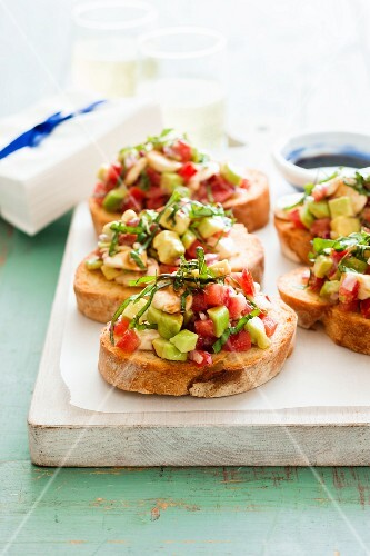 Bruschetta topped with avocado and tomatoes