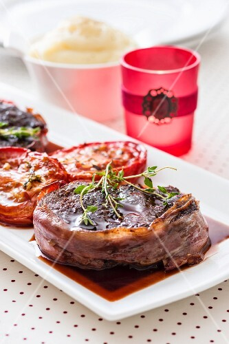 Beef fillet wrapped in bacon with grilled tomatoes