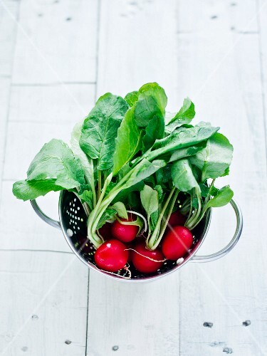 Radishes with leaves in a colander