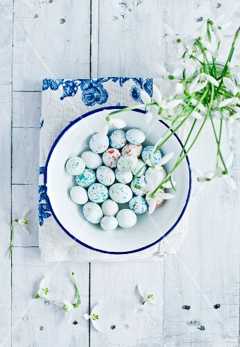 Sugared eggs in an enamel bowl with snowdrops