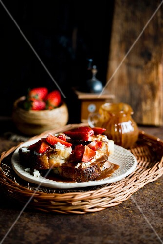 A slice of white bread topped with cream cheese, strawberries and caramel sauce