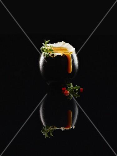 Black Food: Schwarzes Ei, weichgekocht, mit Thymian und Tomatenstückchen auf schwarzem Untergrund mit Reflexion