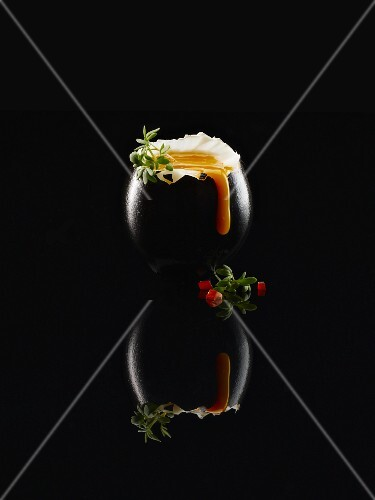 Black food: a soft boiled black egg with thyme and pieces of tomato on a black reflective surface