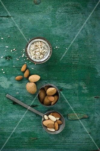Almonds, shelled and unshelled, on a spoon and in a bowl, rustic wooden surface with slivered almonds