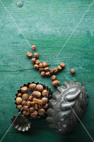 Hazelnuts, shelled and unshelled, in a baking tin on a rustic wooden surface
