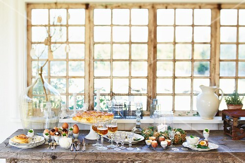 An Easter buffet laid on a wooden table by a window