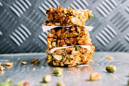 A stack of muesli bars with pistachio nuts and flaxseeds