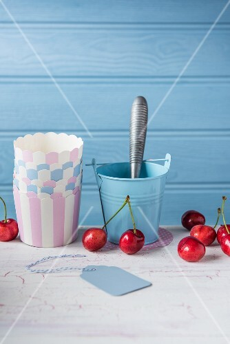 Cherries with paper cups and an ice cream scoop