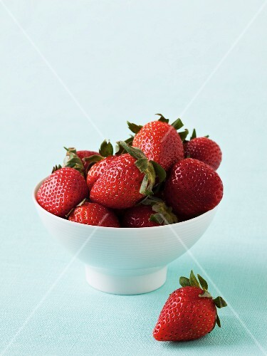 A bowl of strawberries with one next to it