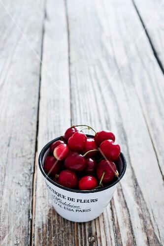 Fresh cherries in an enamel cup