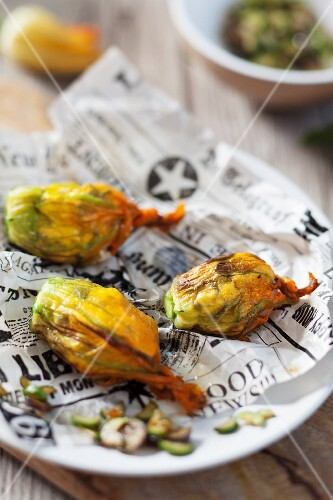 Stuffed courgette flowers on a piece of newspaper on a plate