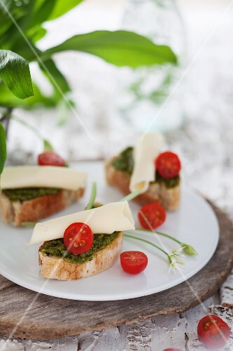 Slices of baguette topped with wild garlic pesto, cheese and cocktail tomatoes