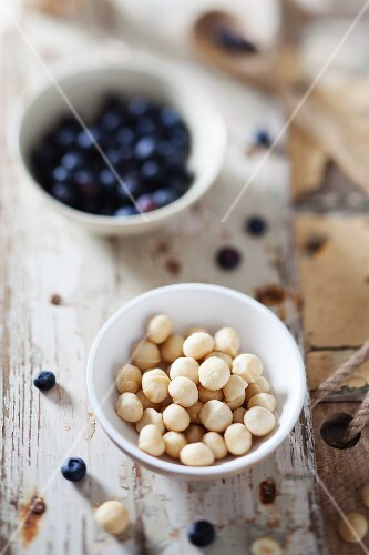 Macadamia nuts and blueberries in bowls on a rustic wooden surface