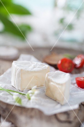 Sliced soft cheese with tomatoes on a wooden board