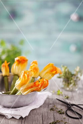 Courgette flowers in a metal bowl