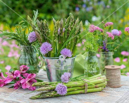 Green asparagus and fresh herbs on a garden table