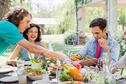 Friends eating together in a garden
