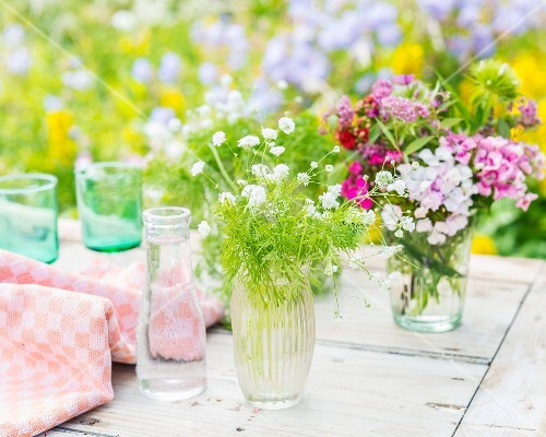 Dill and summer flowers in glass vases