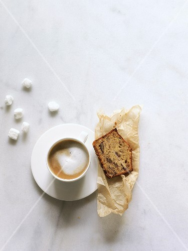 Ein Stück Dattel-Pekannusskuchen zum Cappuccino (Aufsicht)