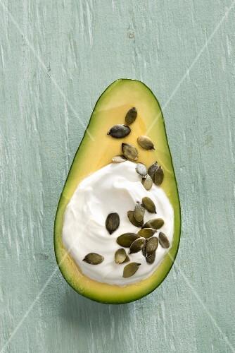 An avocado filled with Greek yoghurt and pumpkin seeds
