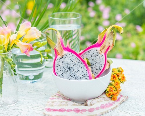 A halved pitahaya (dragon fruit) in a bowl on a garden table