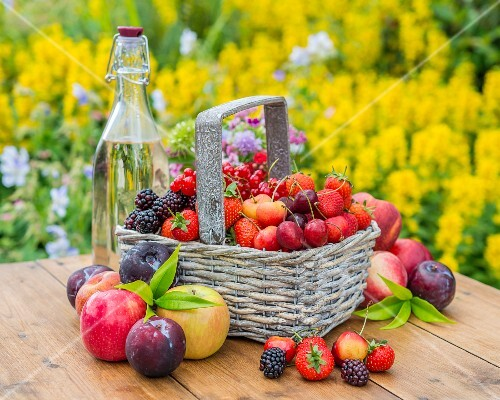 Berries and fruit in a basket and next to it on a garden table