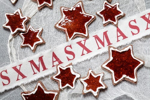 Star shaped almond biscuits filled with redcurrant jelly with Christmas decorations
