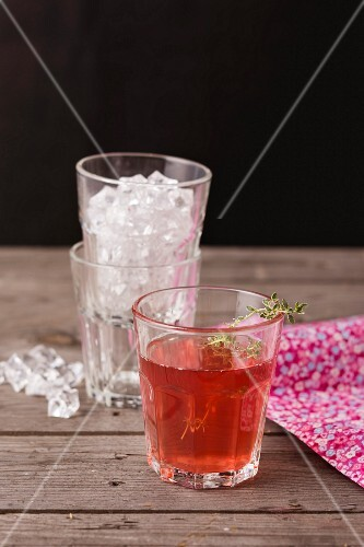 Fruit juice with a sprig of thyme and crushed ice in glasses