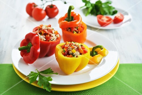 Red, yellow and orange peppers filled with a rice, pepper and tomato salad