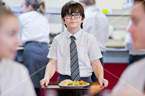 A middle school pupil carrying a lunch tray in the school cafeteria