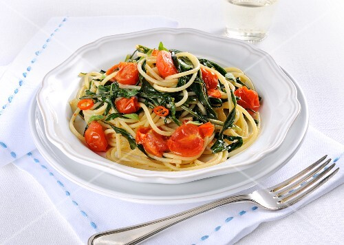Fried spaghetti with dandelions, tomatoes and chilli