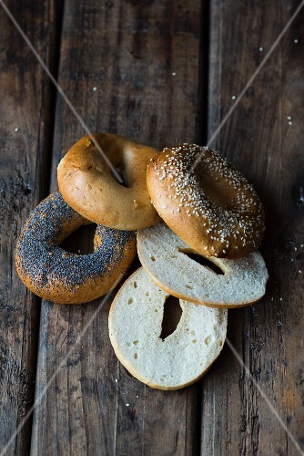 Various bagels on a dark wooden surface