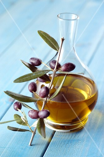 A carafe of olive oil and a sprig of olives