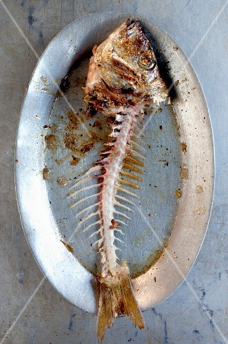 A grilled fish carcass on a plate