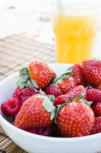 A bowl of strawberries and raspberries with a glass of orange juice in the background