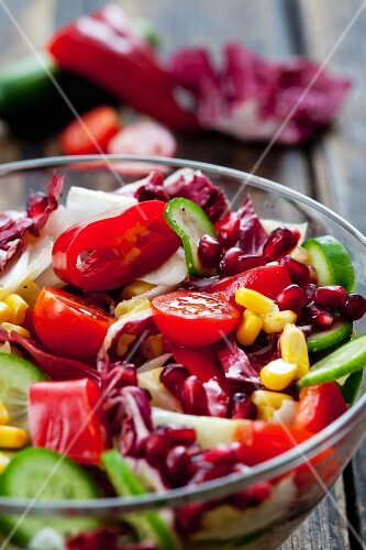 A mixed vegetable salad with pomegranate seeds in a glass bowl (close-up)