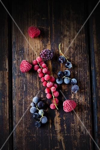 Frozen redcurrants, blackcurrants, raspberries and blackberries on a wooden surface