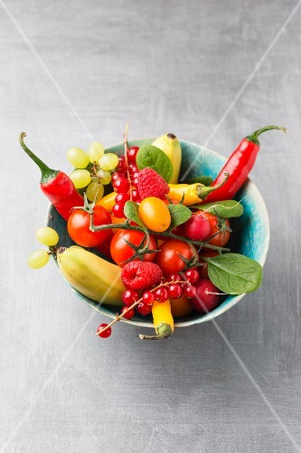 A bowl of various fruit and vegetables on a grey surface