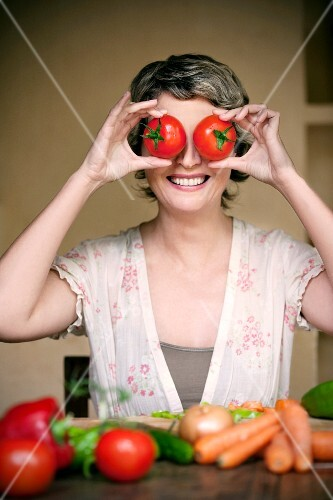 A portrait of a smiling woman holding two tomatoes in front of her eyes