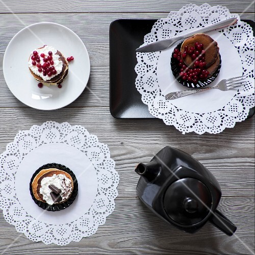 Various dessert tartlets on plates and paper doilies served with tea