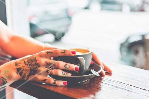A tattooed woman drinking coffee at a bar table in a cafe