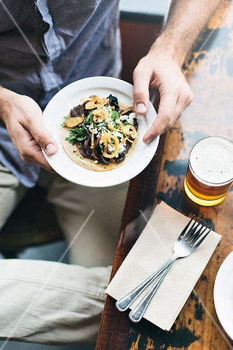 A mn holding a plate with a top tackle with a glass of beer and cutlery next to him on a table