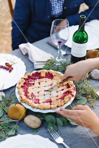 A woman cutting berry pie on an autumnal decorated table outside