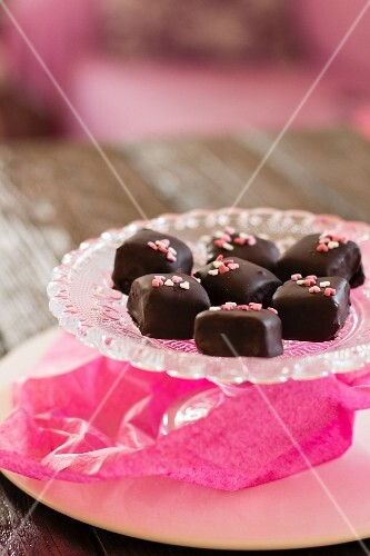 Chocolate pralines with sugar hearts on a crystal plate