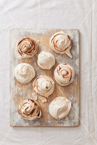 Various meringues with chocolate sauce and strawberries on a weathered wooden board