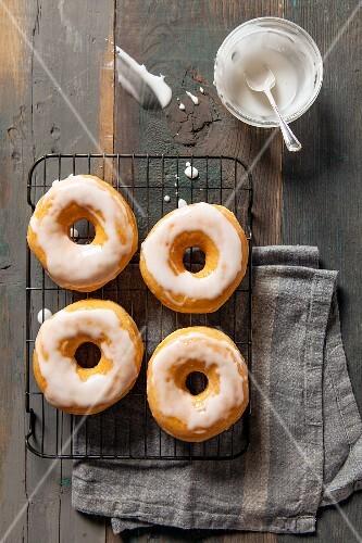 Four glazed doughnuts on a wire rack